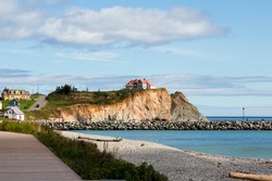 Northern view of the wooden boardwalk along the beach in quaint Percé village, with the Cape Canon, the wharf and a scattering of houses in the background, Quebec, Canada