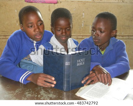 Norton,Zimbabwe,July 13 2015. Primary school children reading  a  bible  inside  their  classroom.Christianity is  the  most  popular religion in southern  Africa.