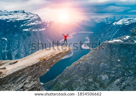 Norway, A woman Jump on the mountain's cliff edge of Trolltunga throning over Ringedalsvatnet  watching the sunset and snowy Norwegian mountains near Odda, Rogaland, Norway Foto stock ©