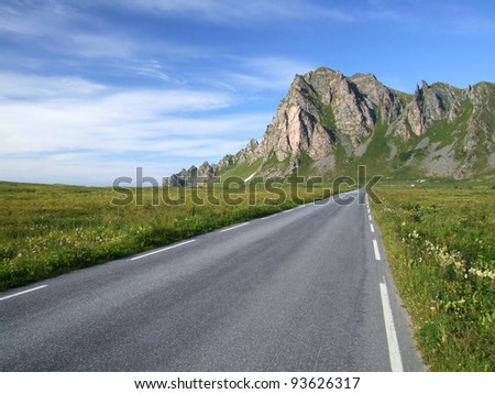 Norway landscape - straight road on Andoya island. Mountains in background.