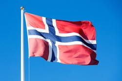 Norway's flag waves in the wind against the blue summer sky
