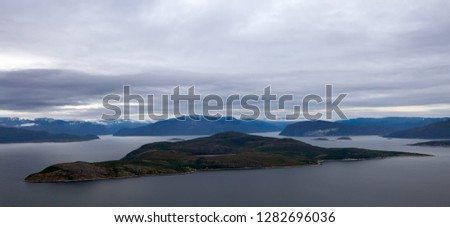 Norway. Summer. In the foreground is a large, elongated island surrounded by water. In the background you can see a lot of fjords and mountains with snow. Gloomy, overcast sky.