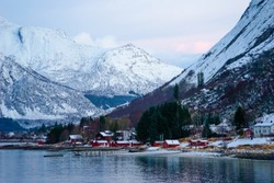 Norway, the village Ornes in December at noon. Typical wooden houses on the coastline an in the background snow covered mountains.