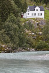 Norwegian antique traditional wooden house, river and hill. Vertical