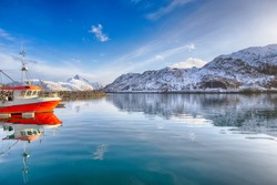 Norwegian Fishing Harbor with One Bright Colorful Fisshing Boat at Peer on Lofoten islands, Norway. Horizontal Image