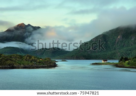 Norwegian fjord surrounded by mountains under the midnight sun #75947821