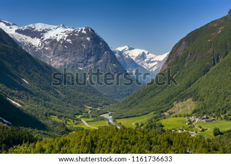 Norwegian landscape with green valley and small village between mountains with snow peaks. Nature and travel background. Jostedalsbreen National Park, Western Norway.