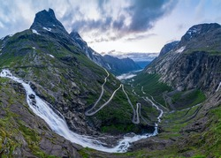 Norwegian mountain road. Trollstigen. Stigfossen waterfall. Midnight sun over the Norway tourist landscape valley.