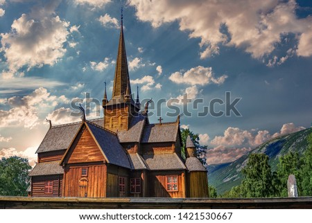 Norwegian stave church in front of blue cloudy sky. Location: Lom, Norway. Name of the church: Lom stave church Stock fotó ©