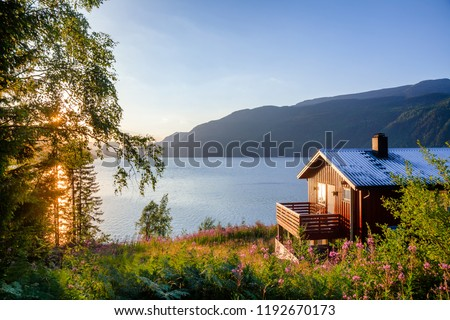 Norwegian wooden summer house (Hytte) with terrace overlooking scenic lake at sunset, Telemark, Norway, Scandinavia