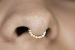 Nose piercing septum. Beautiful piercing jewelry. Macro shot. Selective focus.