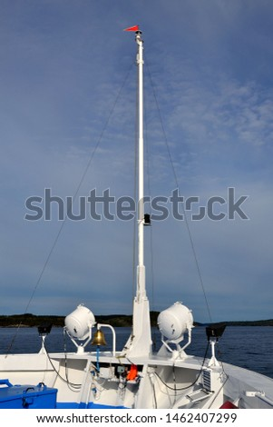 Nose, with a flagpole and a bell of a cruise ship #1462407299