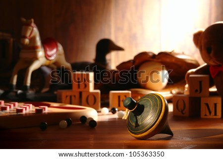 Nostalgic antique wooden spinning top play time toy and traditional collection of old wood children toys with baseball glove and teddy bear with vintage alphabet blocks and marbles in an attic