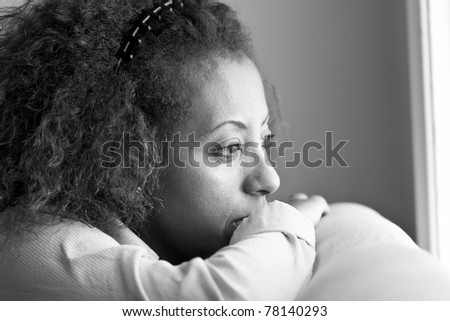 Nostalgic Ethiopian woman looking out the window in deep thought
