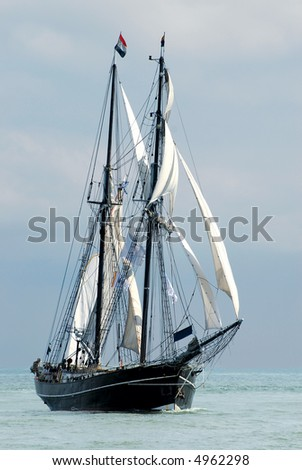 nostalgic sailboat sailing the ocean with cloudy sky background