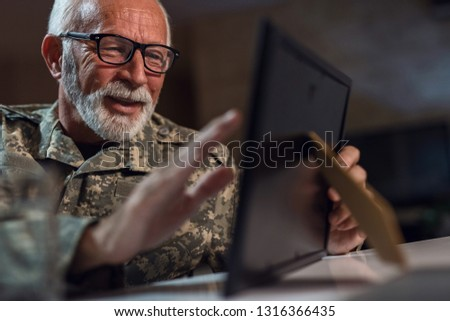 Nostalgic senior veteran recalling the memories and looking at picture in photo frame.
