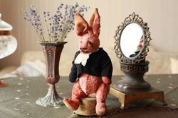 Nostalgic toy teddy rabbit in jacket sitting next to vintage mirror and bouquet of lavender. Selective focus. Concept of collection handmade toys in vintage style. Nostalgic memories from childhood