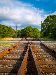 Nostalgic travel landscape and dramatic cloudscape with curved railroads in the forest on Cape Cod