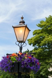 Nostalgic Victorian lamp post with assorted summer flowers hanging in a basket in a public park.