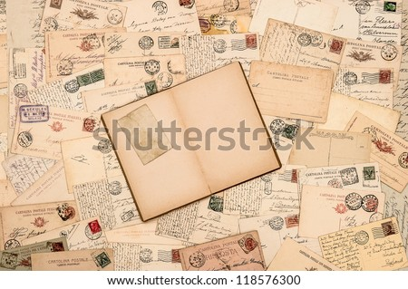 nostalgic vintage background with old handwritten postcards and open empty book page