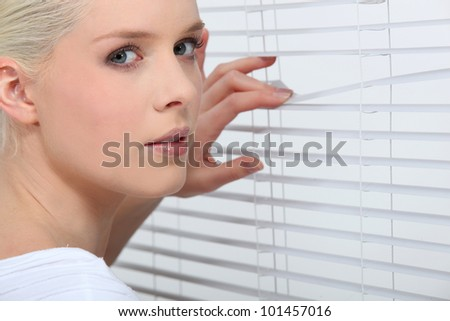 Nosy blond peering through window blinds