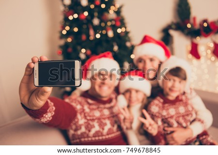 Not clear view of four bonding relatives, at home, married couple, parents, mom and dad, siblings show v sign peace two fingers gesture, in knitted cute traditional x mas costumes, friendship, love