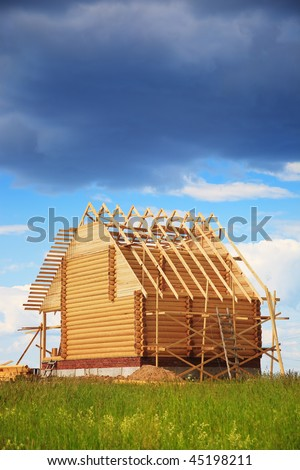 Not completed wooden house under the big dark cloud