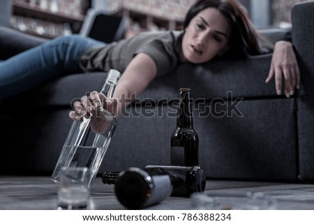 Not enough. Selective focus of a bottle with alcohol being taken by a drunk unhappy woman while lying on the sofa Сток-фото ©