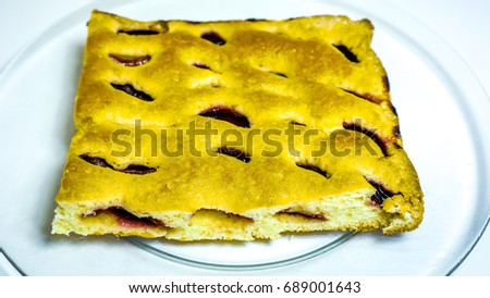 not finished homemade cake made of raw dough with plumps and texture-baked dough cut into square against clear glass plate. Peace of home holiday cake as best addition to a cup of coffee or tea