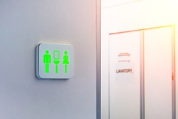Not occupied toilet sign is marked in green, against the background is a door from the wc inside the plane