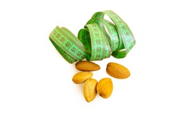 not peeled almonds and green centimeter letta on a white isolated background. about the benefits of nuts when losing weight