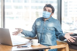 Not sure! Portrait of confused young man with medical mask in blue shirt sitting, working on laptop with raised arms and puzzled face, looking at camera. indoor working and health care concept.