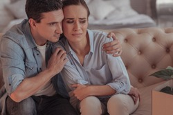 Not worth your tears. Waist up of calm sympathizing husband hugging his downhearted upset wife while sitting on the sofa