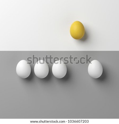 Notable yellow egg with white eggs on white and grey background.minimal style