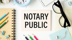 NOTARY PUBLIC is written in a white notepad near a calculator, coffee, glasses and a pen. Business concept