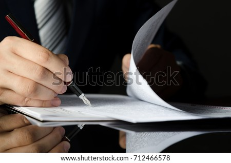 Notary signing a contract with fountain pen in dark room concept. pen business man law attorney lawyer notary public #712466578