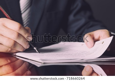 Notary signing a contract with fountain pen in dark room concept. pen business man law attorney lawyer notary public