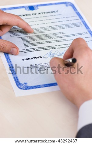 notary signing a power of attorney, focus is on the tip of the pen. Document was created by the photographer.