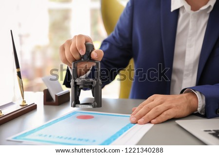 Notary stamping document at desk in office, closeup #1221340288