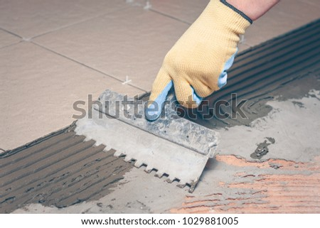 notched trowel in the hands of the tiler