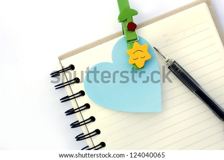 Note book and a pen on white background