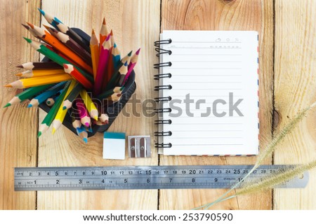 Note book and color pencils on wooden background - vintage effect style pictures