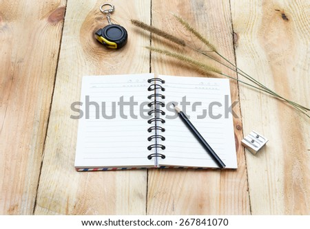 Note book and pencil on wooden background - vintage effect style pictures