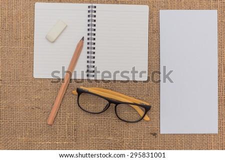 note book ,pencils,eraser,glasses,envelope on sack background