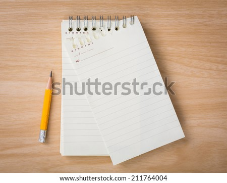 Note book with pencil on a wooden desk
