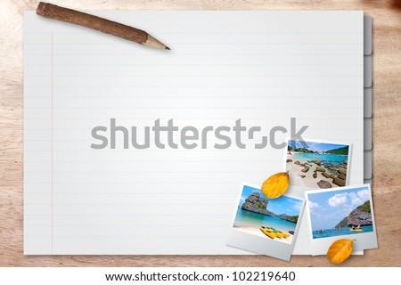 Note book with photo frame on wood background