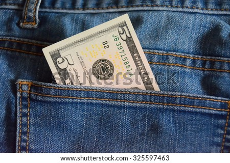 note of five dollars in the jeans pocket, closeup