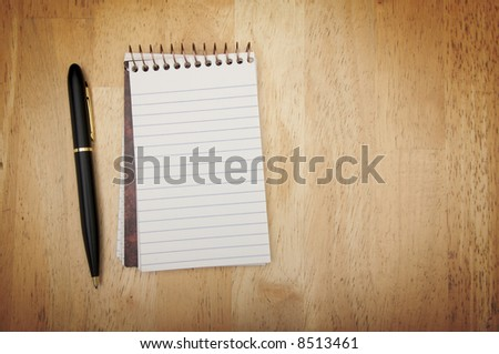 Note Pad and Pen on Wood Background
