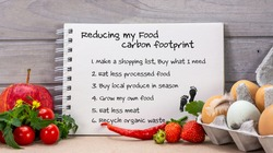 Note pad with Reducing my food carbon footprint heading and list of ways to reduce carbon pollution at home, sustainable living and ethical consumerism.
