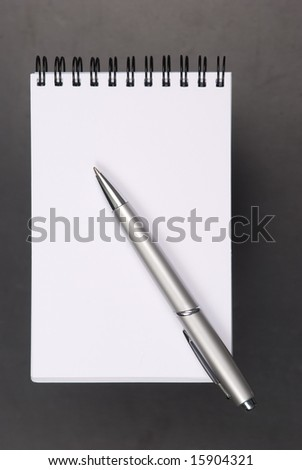 Note paper and opened notebook and the pencil